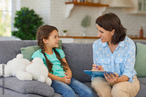 Obraz Happy little child communicating with psychologist sitting on sofa during therapy session at home - fototapety do salonu