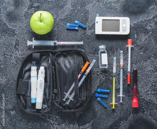 Fényképezés Glucometer, lancet pens, blood sample, syringes and insulin on dark background