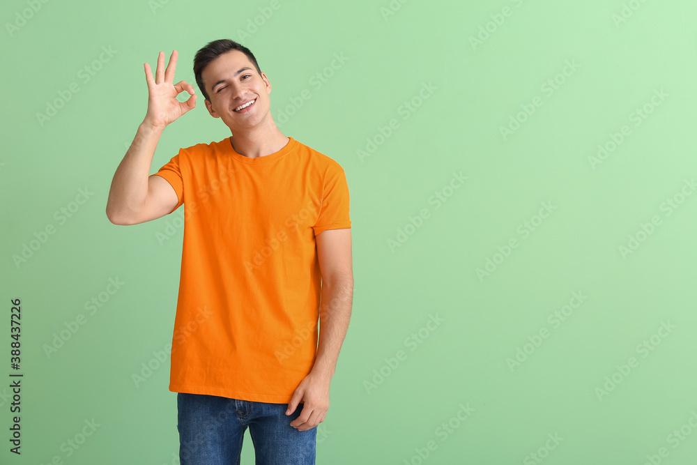 Fototapeta Handsome young man in orange t-shirt showing OK on color background