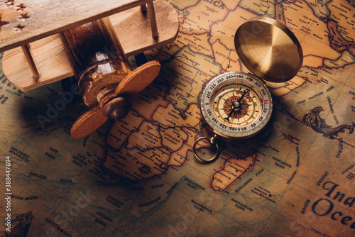 Fotografering Old compass discovery and wooden plane on vintage paper antique world map backgr