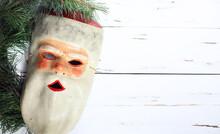 Old Vintage Retro Papier Mache Ugly/unusual Mask Of Santa Claus On White Wooden Background. Merry Christmas And Happy New Year 2021 Postcard Design. Copy Space For Message.