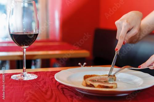 Foto ナイフとフォークで肉料理を食べているシーン ワイングラスと赤ワイン