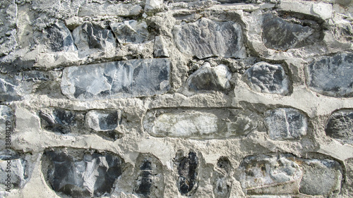 Fotografiet A historic village house wall was built with a rocks collected from a near river