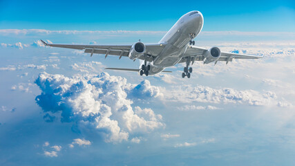 Commercial airplane flying above blue sky and white clouds.
