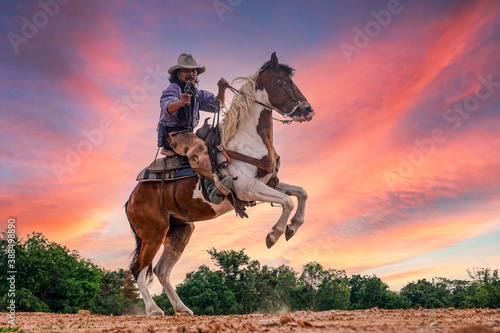 Silhouette and blur of action cowboy holding a gun on horseback.
