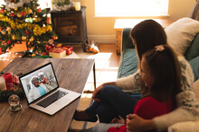 Woman And Daughter Sitting On Couch Having A Videocall With Santa Claus And Senior Woman In Santa Ha