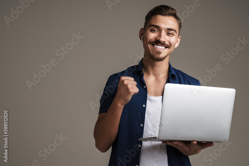 Obraz Image of happy handsome guy showing winner gesture while holding laptop - fototapety do salonu