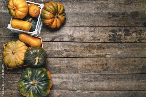 Cuadros en Lienzo Pile of pumpkins in wooden box on wooden board