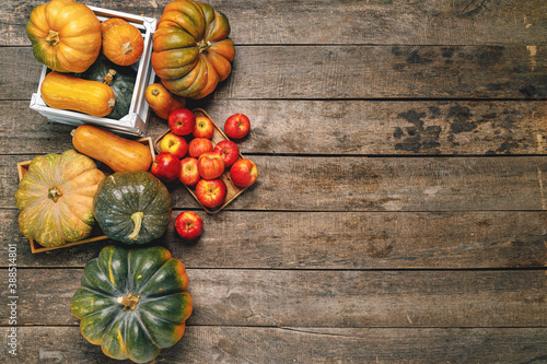 Fotografía Pile of red apples and pumpkins on wooden surface