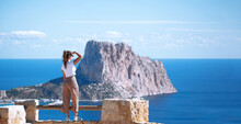 Calpe Coast, Tourist Woman Looking At Calpe Or Calp Coast And Penon The Ifach Or Penyal D'Ifac Natural Park From Path Above The City In The Morro De Toix