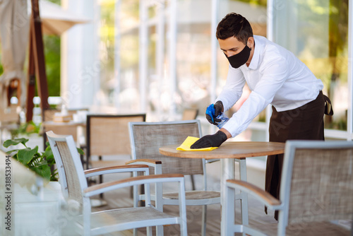 Fotografia Waiter in protective face mask and gloves cleaning the table with disinfectant spray in a restaurant