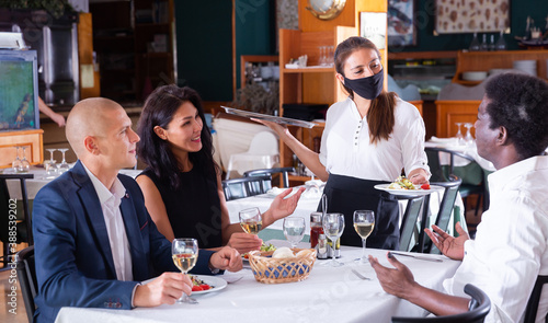 Fototapeta Hospitable waitress wearing face protective mask bringing ordered meals to guests. New normal restaurant concept in coronavirus pandemic .. obraz