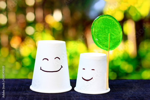 Obraz na plátne Two smiling cups with green lollipop