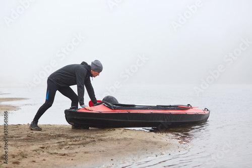 Fotografía Man pulling canoe into water, wearing black clothing, posing on bank of river, handsome sports man doing water sport in foggy autumn day, canoeing in cloudy morning