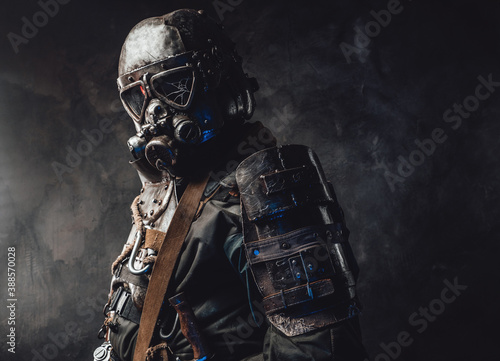 Fotografia Epidemic and apocalyptic survivor dressed in his custom dark armour and gas mask with broken glass in dark background