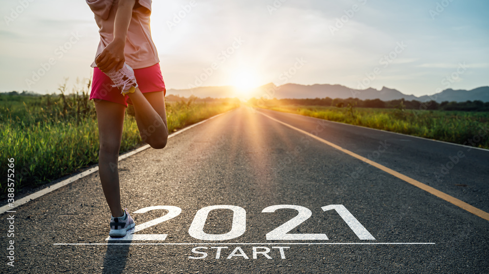 Fototapeta New year 2021 or start straight concept.word 2021 written on the asphalt road and athlete woman runner stretching leg preparing for new year at sunset.Concept of challenge or career path and change.