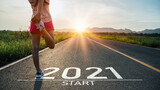 Fototapeta Kawa jest smaczna - New year 2021 or start straight concept.word 2021 written on the asphalt road and athlete woman runner stretching leg preparing for new year at sunset.Concept of challenge or career path and change.