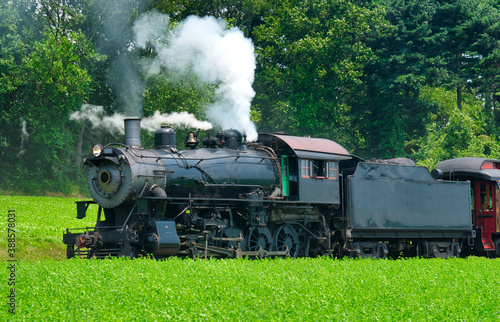 Fototapeta Close Up of an Antique Steam Passenger Train Puffing along Amish Countryside with Green Fields obraz na płótnie