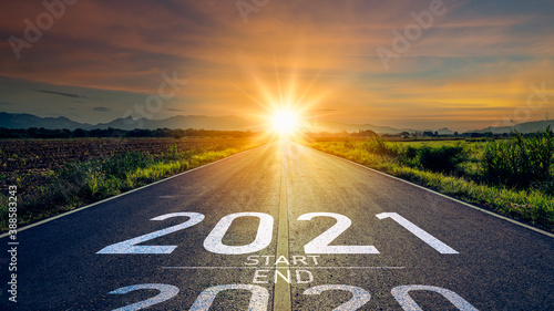 New year 2021 or start straight concept.word 2021 written on the road in the middle of asphalt road at sunset.Concept of planning and challenge or career path,business strategy,opportunity and change
