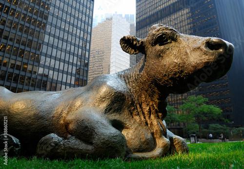 Naklejka premium Bronze bull lying in grass among financial towers, Toronto, Canada - September 8, 2006