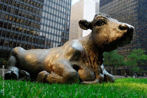 Naklejka premium Bronze bull lying in grass among bank towers and working businessman, Toronto, Canada - September 8, 2006