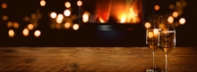 Champagne On Rustic Wood In Front Of A Log Fire With Golden Bokeh Lights. Horizontal Background For Celebrations And Cozy Evenings With Space For Your Text And Decorations.