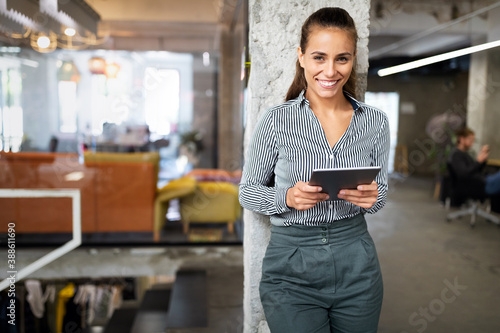 Obraz Portrait of cute confident business woman with digital tablet in office - fototapety do salonu