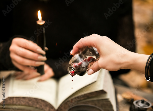 Canvas Print The witch conducts a ritual, drips wine on the witchcraft book