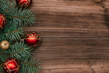 Frame Made Of Christmas Tree Branches  With Red And Gold  Balls On A Dark Wooden Background.New Year,Christmas Concept. Copy Space For Text,top View, Selective Focus With Shallow Depth Of Field