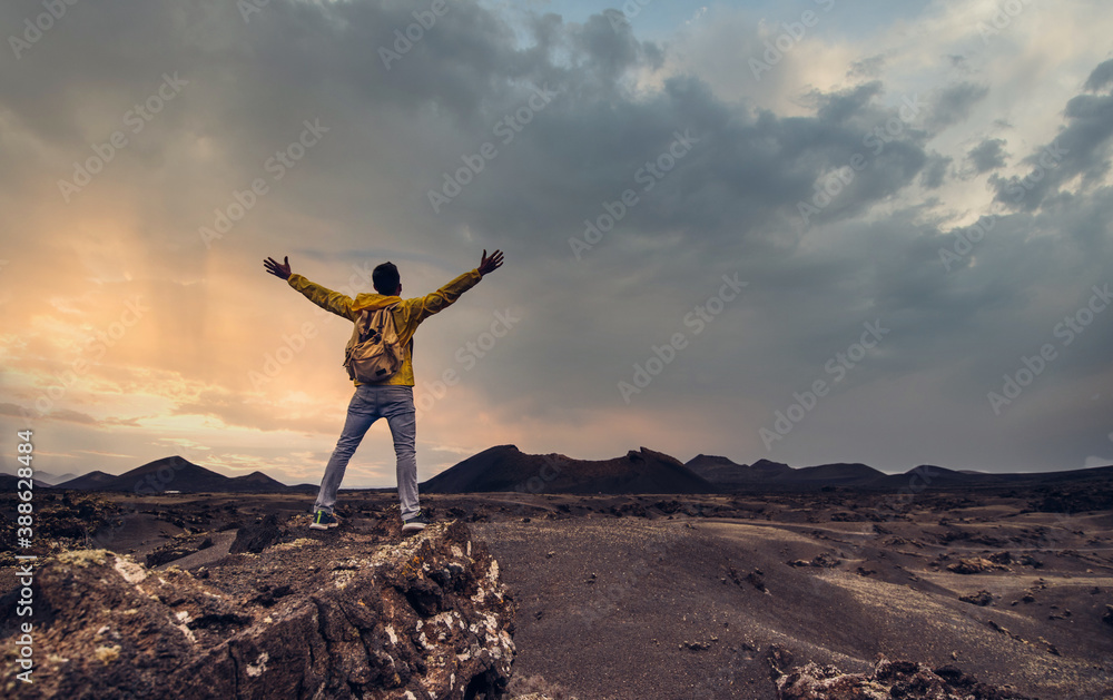 Fototapeta Hiker celebrating success on top of a mountain at sunset - Success, winner and sport concept.