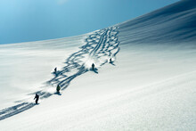 A Group Of Heli Skiers Come Down The Mountain