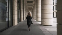 A Girl Walking Among Columns With Her Back Turned To Camera. Action. Rear View Of A Woman With Curly Hair Walking Outdoors Near The Building With Big Windows And Giant Pillars.