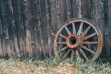 One Rusty Wagon Wheels Against A Wooden Wall, With Grass. Useful For Rustic Backgrounds