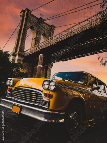 Vintage yellow taxi cab in New York under the Brooklyn Bridge with a colorful sk Poster Mural XXL