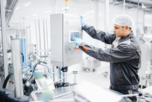Male Operator Engineer Controls Production Line From Control Panel, Food Factory