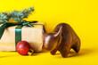 Leinwandbild Motiv Figurine of bull and New Year gift on color background