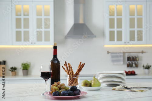 Red wine and snacks on white table in modern kitchen. Space for text