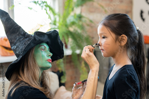 Photo Concentrated young woman with green face painting whiskers on kids face while pr