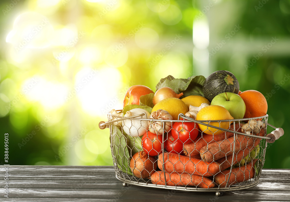 Fototapeta Variety of fresh delicious vegetables and fruits in basket on table against blurred background, space for text