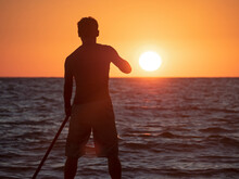 Silhouette Of Active Man Rowing With Paddle On SUP At Sun Background