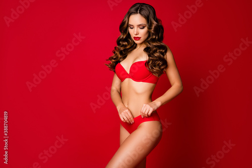 Photo of attractive beautiful seduce curly lady model advertising underwear novelty sensual slim fit body fixing soft bikini wear brassiere panties isolated red color background