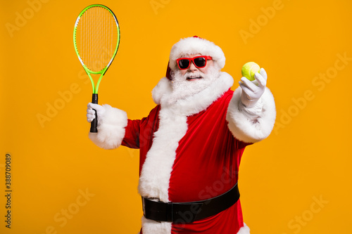 Obraz Portrait of his he nice attractive cheerful cheery glad Santa enjoying playing badminton hobby activity festal day isolated over bright vivid shine vibrant yellow color background - fototapety do salonu