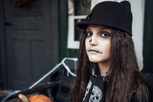 Beautiful Scary Little Girl Celebrating Halloween. Terrifying Black, White Half-face Makeup And Witch Costume, Stylish Image. Horror, Fun At Children's Party In Barn On Street. Hat, Fur Coat, Chain