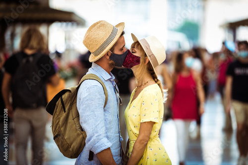 Fotografie, Obraz Tourist with face mask kissing in the city - New normal lifestyle concept with couple in love kiss outdoor - Tourism, love and corona virus