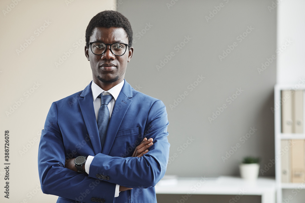 Fototapeta Portrait of African young businessman in eyeglasses and in formalwear standing with his arms crossed and looking at camera