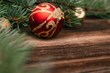 Christmas Tree Branches Close Up With Red And Gold  Balls On A Dark Wooden Background.New Year,Christmas Concept. Copy Space For Text,selective Focus With Shallow Depth Of Field