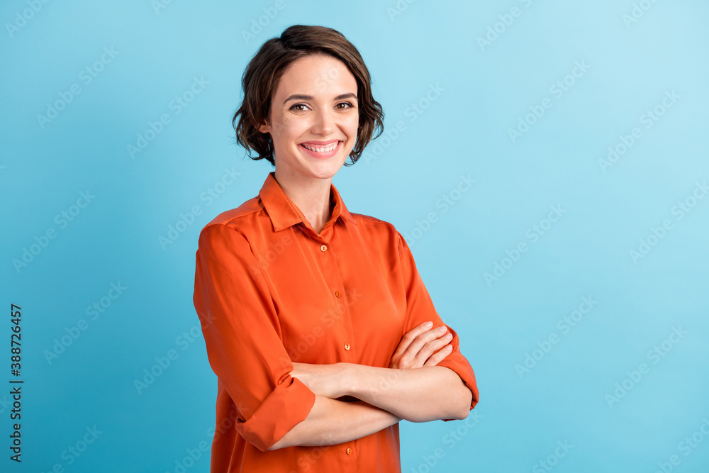 Fototapeta Photo of pretty attractive lady bobbed hairdo arms crossed self-confident person worker friendly smile white teeth good mood wear orange office shirt isolated blue color background