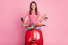 Photo Portrait Of Curious Girl Sitting On Red Motorcycle Pointing At Empty Space Smiling Isolated On Pastel Pink Color Background