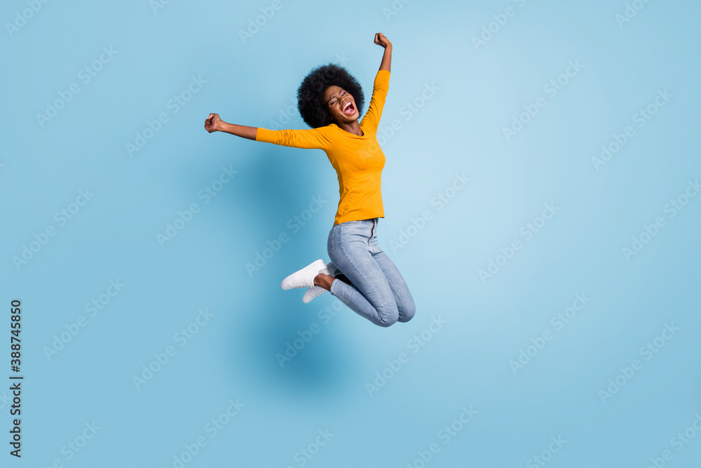 Fototapeta Photo portrait full body of excited girl celebrating jumping up isolated on pastel blue colored background