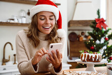 Happy Woman In Santa Claus Hat Smiling While Using Mobile Phone